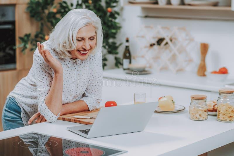 La señora madura sonriente está mirando el ordenador portátil en cocina imagen de archivo libre de regalías