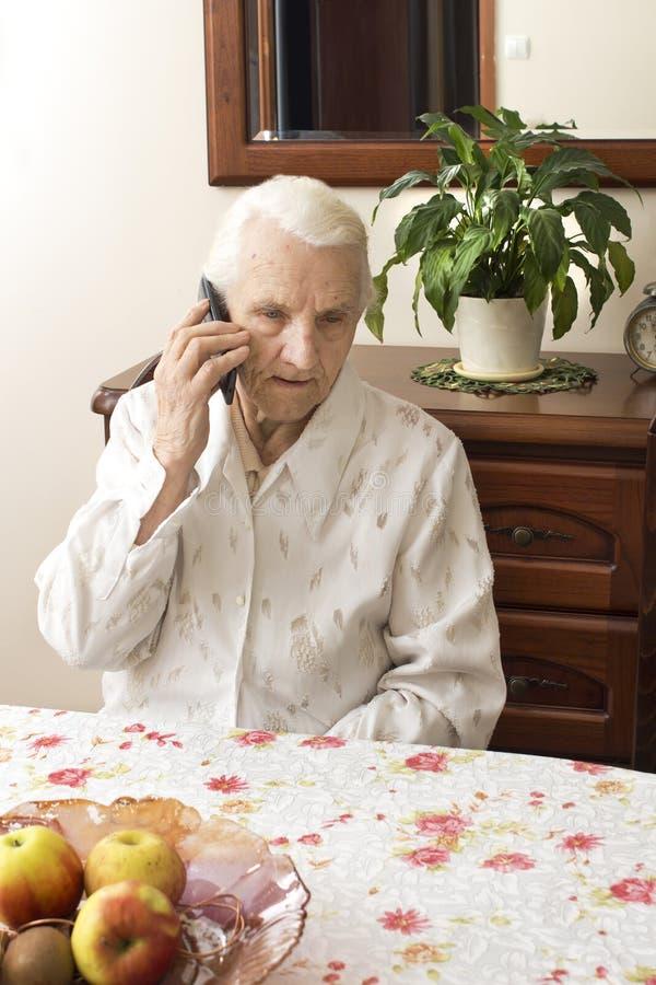 La señora mayor que habla en un teléfono celular mientras que se sienta en una tabla en la sala de estar imágenes de archivo libres de regalías