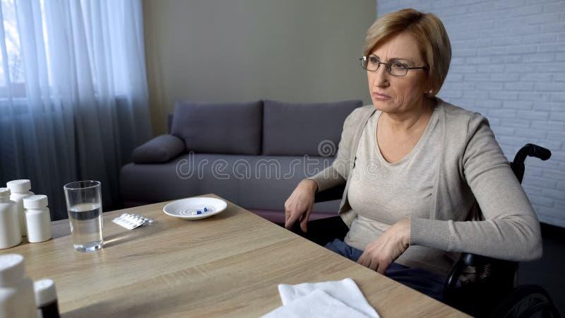 La señora mayor que se sienta en silla de ruedas en la tabla siente sola y deprimida, clínica de reposo imagen de archivo