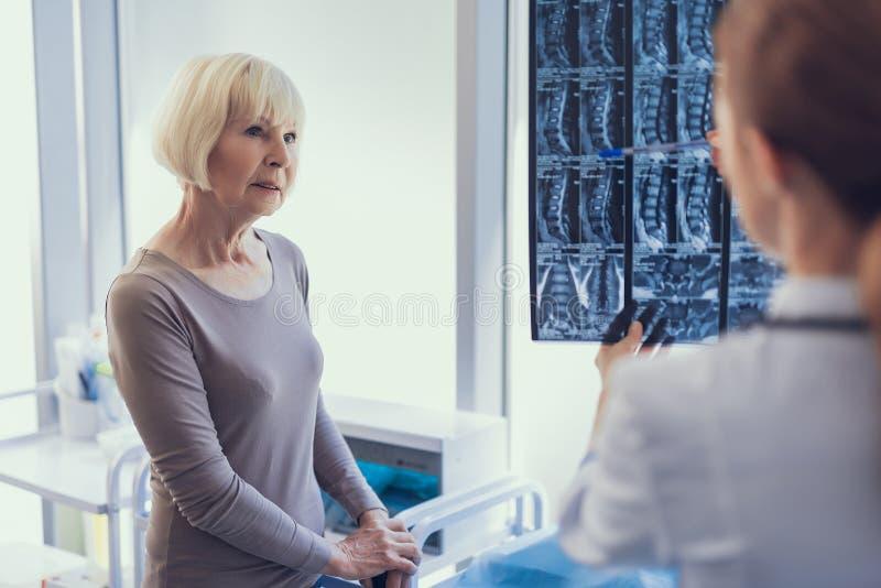 La señora mayor seria está consiguiendo resultados radiológicos de doctor foto de archivo
