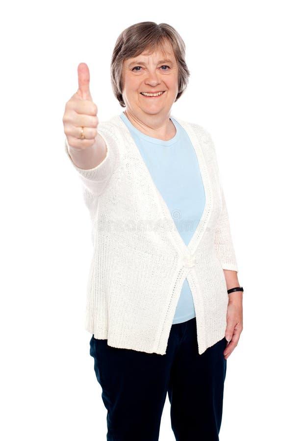 La señora mayor sonriente que muestra los pulgares sube gesto fotografía de archivo libre de regalías