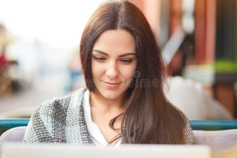 La señora morena hermosa enfocada en ordenador portátil, tiene expresión contenta, presenta en cafetería al aire libre, charla en fotografía de archivo libre de regalías