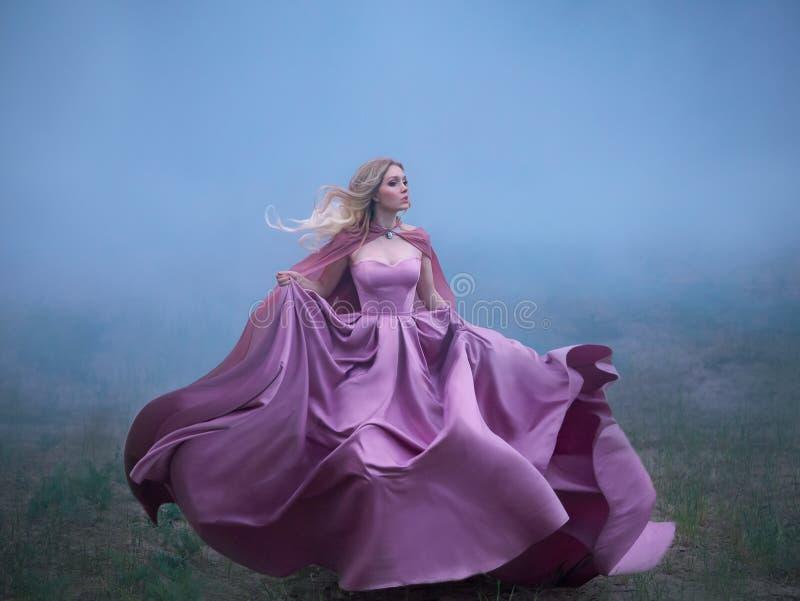 La señora rubia misteriosa excelente corre lejos de una pesadilla, monstruo del bosque, su vestido real costoso largo ligero fotos de archivo libres de regalías