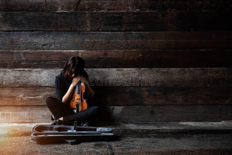 La señora se está sentando en piso del cemento de la superficie del grunge, violín del control y arco en sus brazos, cara de la v fotografía de archivo libre de regalías