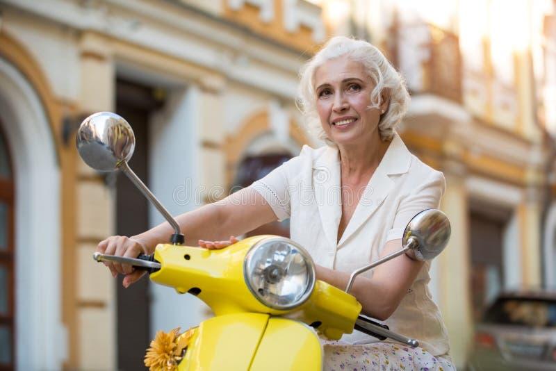 La señora toca el scooter& x27; volante de s foto de archivo libre de regalías