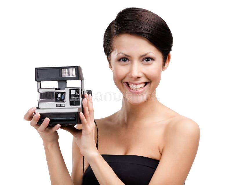 La señora toma las fotos con la cámara del cassette imagen de archivo