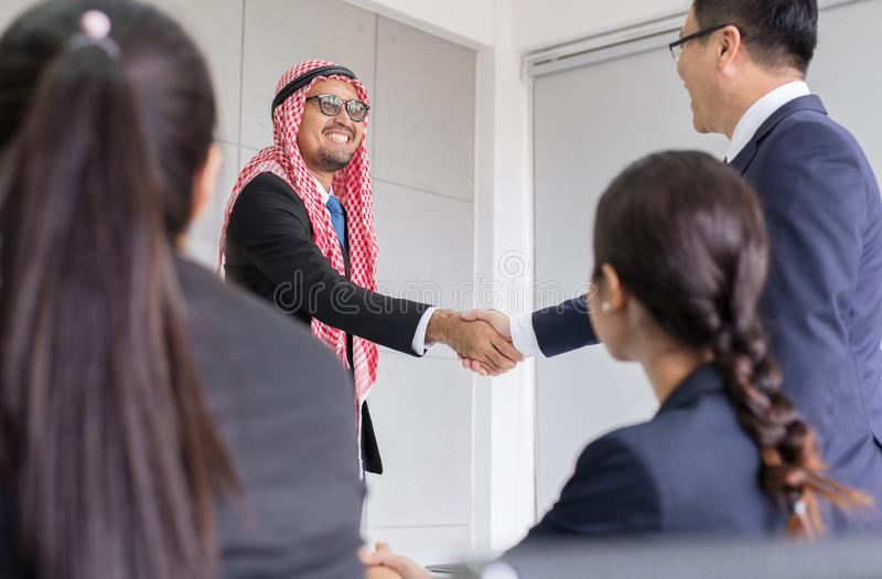 La secousse arabe d'homme d'affaires remettent une affaire aux personnes d'associé, réussies et heureuses d'association finissant photographie stock libre de droits