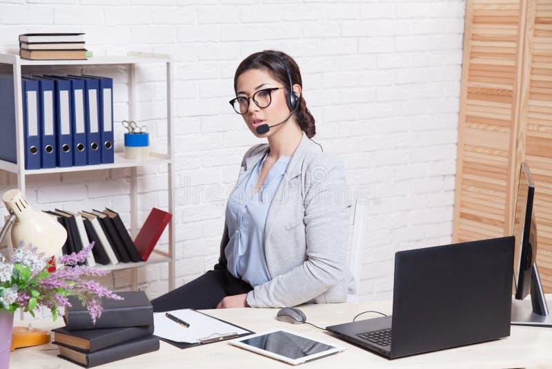 La secrétaire de fille d'affaires s'assied à un centre d'appels blanc de bureau image stock