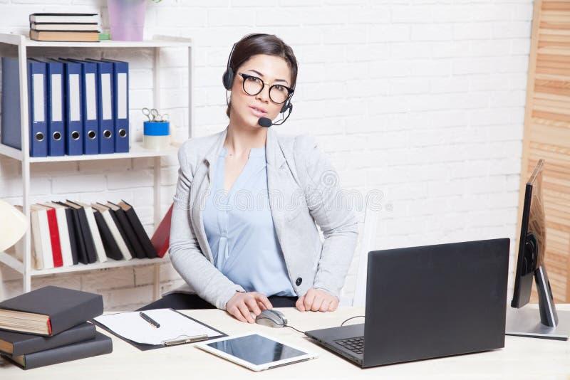 La secrétaire de fille d'affaires s'assied à un centre d'appels blanc de bureau image libre de droits