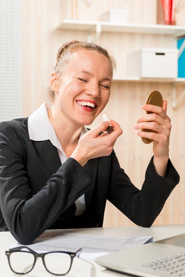 La secretaria de risa corrige maquillaje en el lugar de trabajo fotografía de archivo