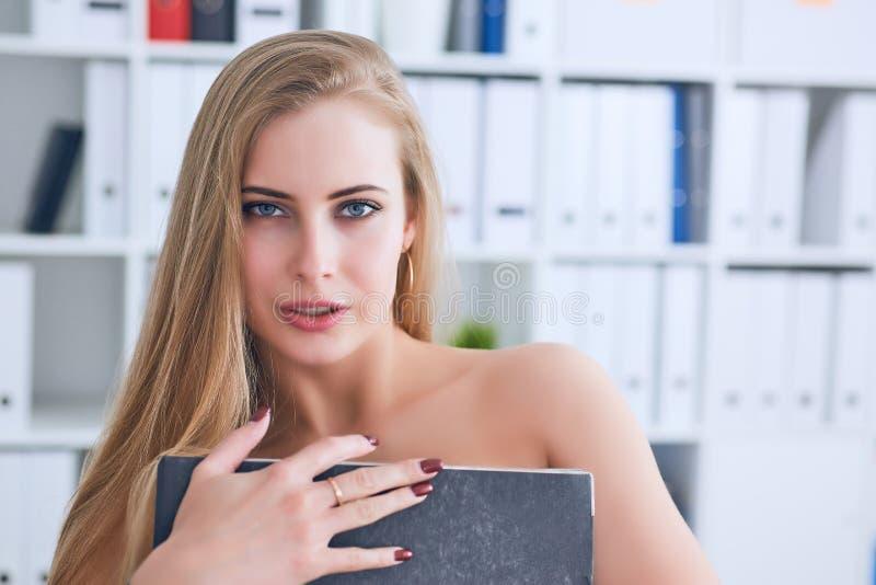 La secretaria joven hermosa oculta su desnudez para una carpeta en un fondo de la oficina Concepto del acoso imagen de archivo libre de regalías