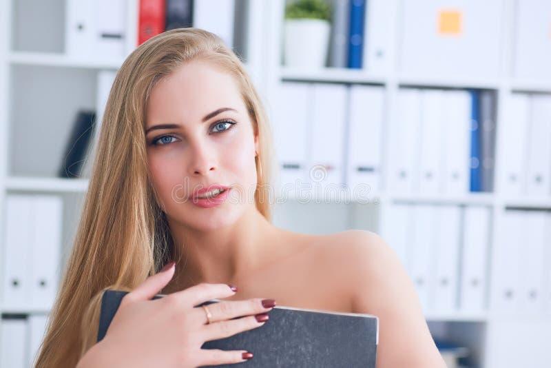 La secretaria joven hermosa oculta su desnudez para una carpeta en un fondo de la oficina Concepto del acoso fotos de archivo
