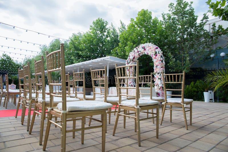 La sede di nozze con un arco del fiore immagini stock