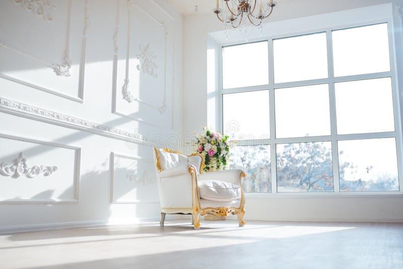 La sedia d'annata di stile del cuoio bianco nella stanza interna classica con la grandi finestra e molla fiorisce immagine stock libera da diritti