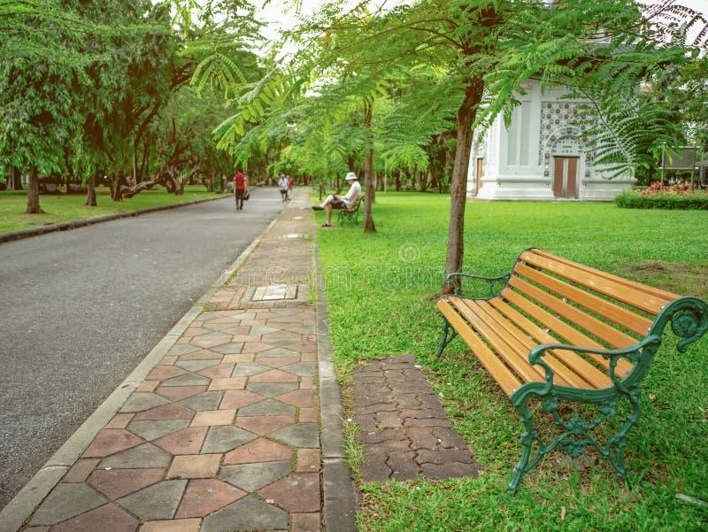 La sedia di legno nel parco verde e la gente si rilassano nel parco fotografia stock