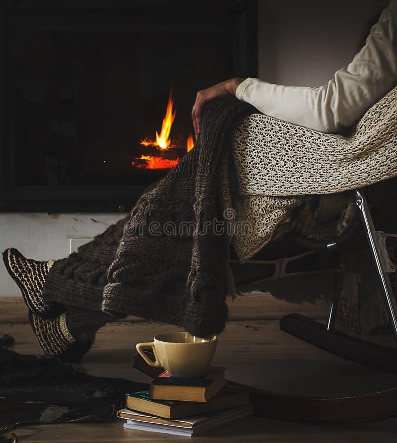La sedia di oscillazione con tricotta la coperta, i libri e la tazza di tè o di caffè prima del camino immagini stock libere da diritti