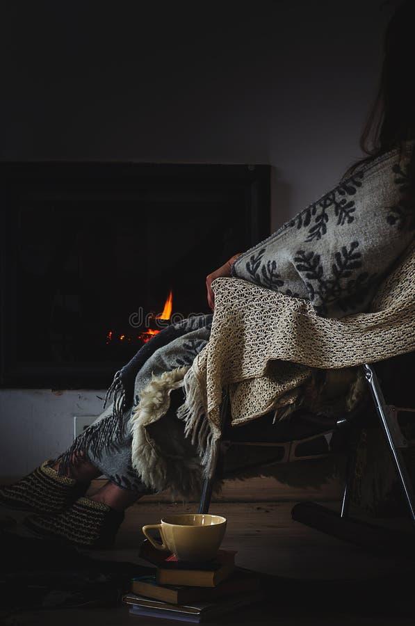 La sedia di oscillazione con tricotta la coperta, i libri e la tazza di tè o di caffè prima del camino fotografie stock libere da diritti
