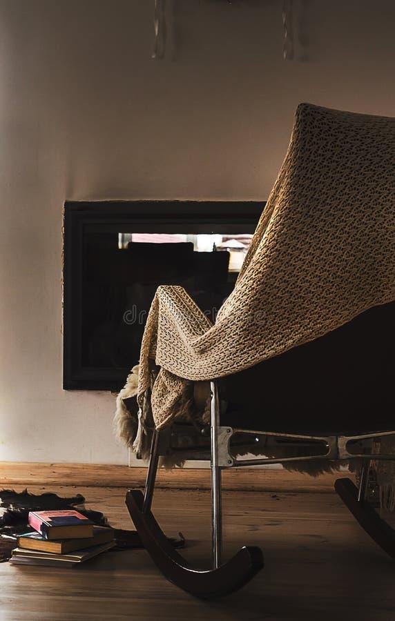 La sedia di oscillazione con tricotta la coperta, i libri e la tazza di tè o di caffè prima del camino fotografia stock libera da diritti