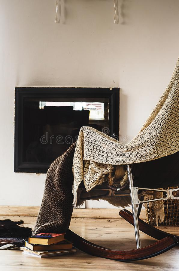 La sedia di oscillazione con tricotta la coperta, i libri e la tazza di tè o di caffè prima del camino fotografia stock