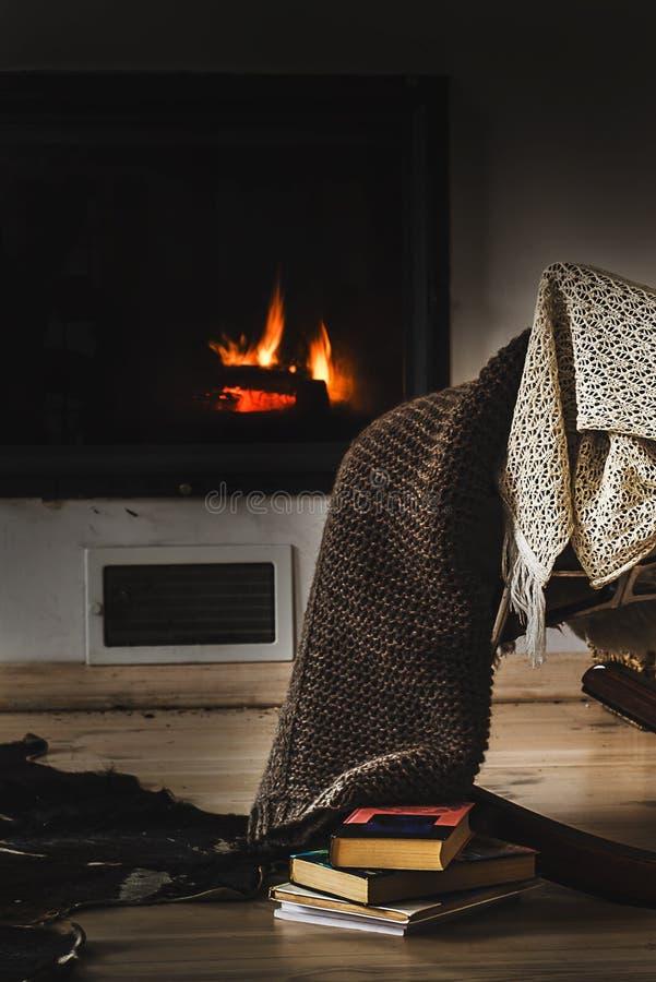 La sedia di oscillazione con tricotta la coperta, i libri e la tazza di tè o di caffè prima del camino immagini stock