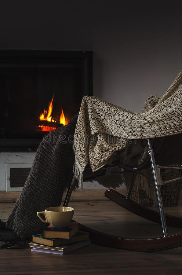 La sedia di oscillazione con tricotta la coperta, i libri e la tazza di tè o di caffè prima del camino immagine stock libera da diritti