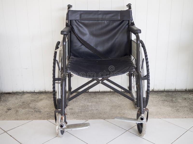 La sedia a rotelle abbandonata e la parete bianca backgroundabandoned la sedia a rotelle ed il fondo bianco della parete fotografia stock libera da diritti