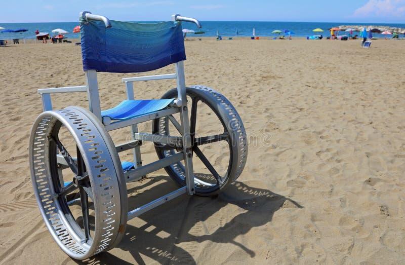 La sedia a rotelle speciale con grande spinge dentro l'alluminio sulla spiaggia fotografia stock libera da diritti