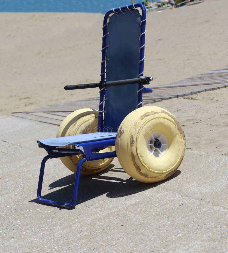 La sedia a rotelle speciale con i grandi galleggianti spinge per andare nel mare immagini stock libere da diritti