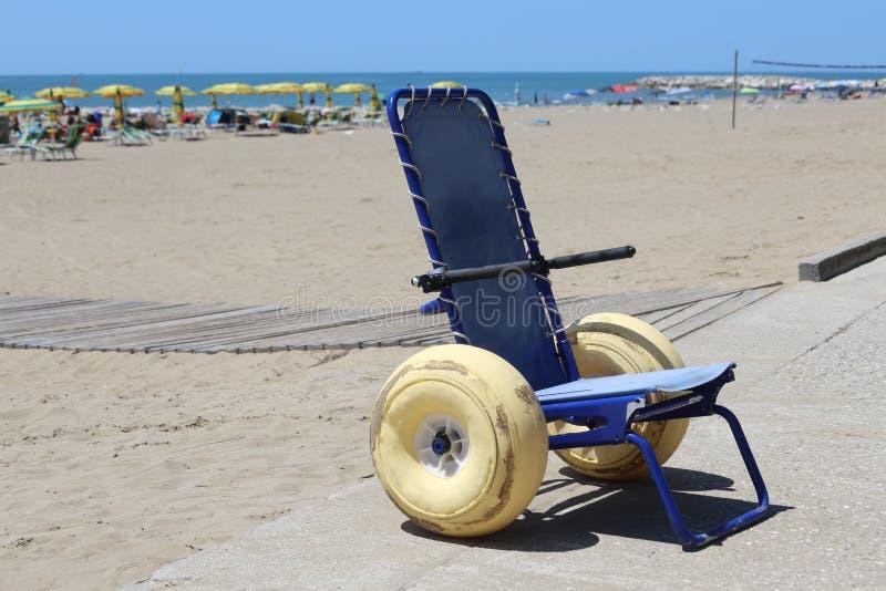La sedia a rotelle speciale con i grandi galleggianti spinge per andare nel mare dentro immagini stock