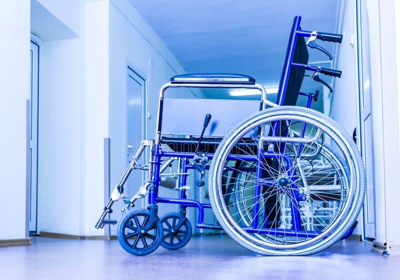 La sedia a rotelle vuota che parcheggia al modo della passeggiata dell'ospedale prepara per la persona portata di inabilità Costr fotografie stock