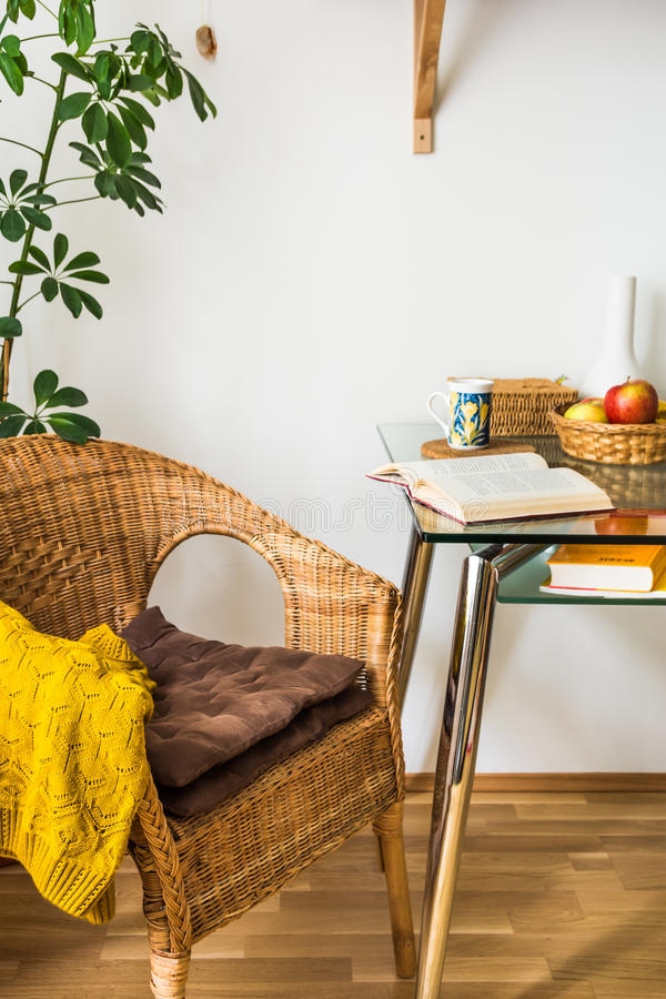 La sedia tessuta interna del rattan del salone, cuscini, ha tricottato il maglione, il libro aperto, la tazza di tè, i frutti in  immagine stock libera da diritti