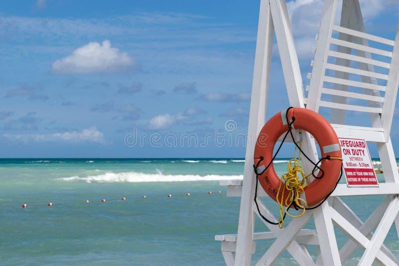 La sedia/torre vuote del bagnino con le ore in servizio firma immagine stock libera da diritti