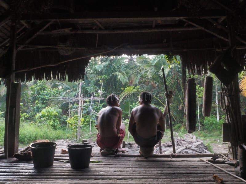 La seduta degli uomini di Mentawai nella casa della giungla immagine stock