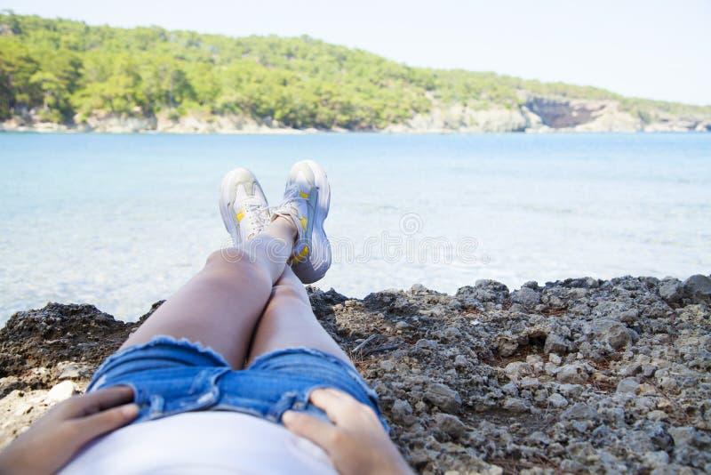 La seduta felice della giovane donna, gode della vita sulla spiaggia in mare fotografia stock