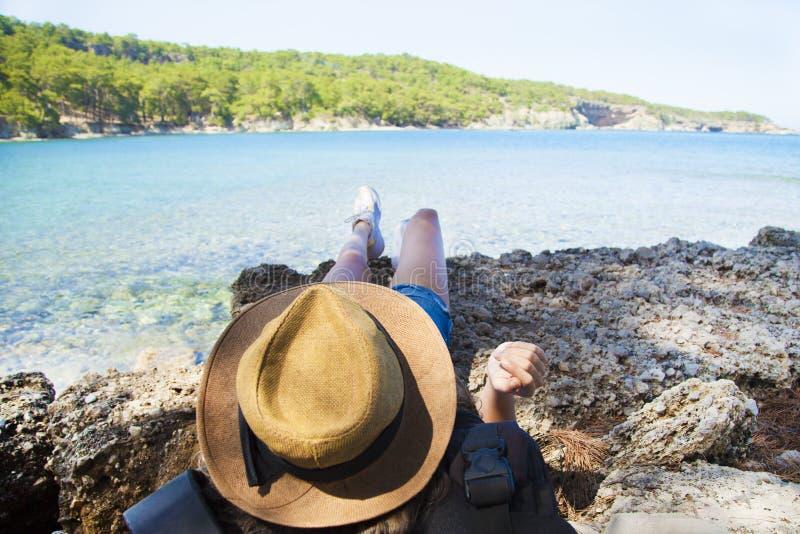 La seduta felice della giovane donna, gode della vita sulla spiaggia in mare fotografie stock libere da diritti