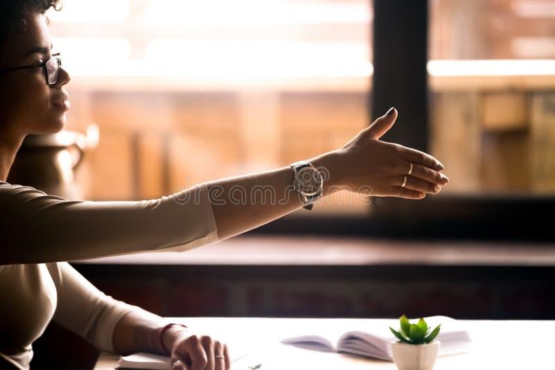 La seduta femminile alla tavola dà la sua mano per la stretta di mano immagine stock libera da diritti
