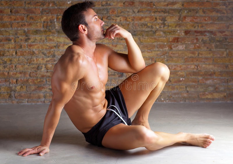 La seduta a forma di dell'uomo del muscolo si è distesa su brickwall fotografia stock
