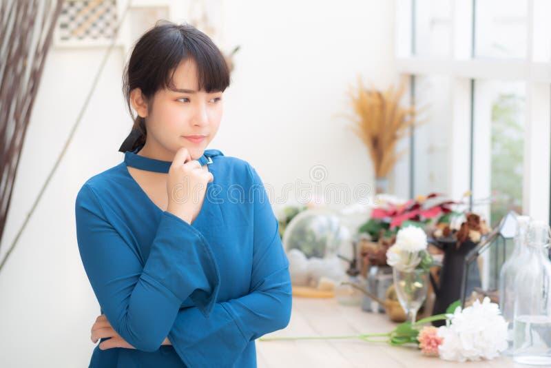 La seduta sorridente della bella donna asiatica del ritratto giovane al caff?, ragazza di modello soddisfatta di si rilassa e rip fotografia stock libera da diritti