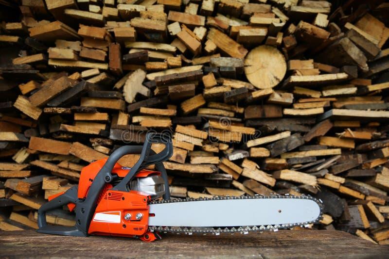 La sega di Chainsaw si trova sullo sfondo di legna da ardere segata immagini stock