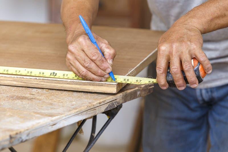 La sega di uso del carpentiere ha tagliato il legno per fa la nuova mobilia fotografia stock