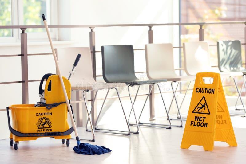 La segnaletica di sicurezza con il pavimento bagnato di cautela di frase e la zazzera bucket, all'interno immagine stock