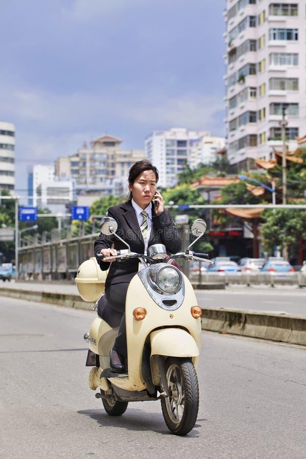 La segretaria fa la telefonata sulla e-bici, Kunming, porcellana fotografia stock libera da diritti