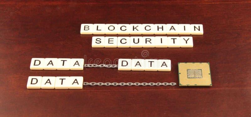 La seguridad de la cadena de bloque deletreó hacia fuera en tejas en un fondo de madera de la cereza con datos y un microprocesad imágenes de archivo libres de regalías