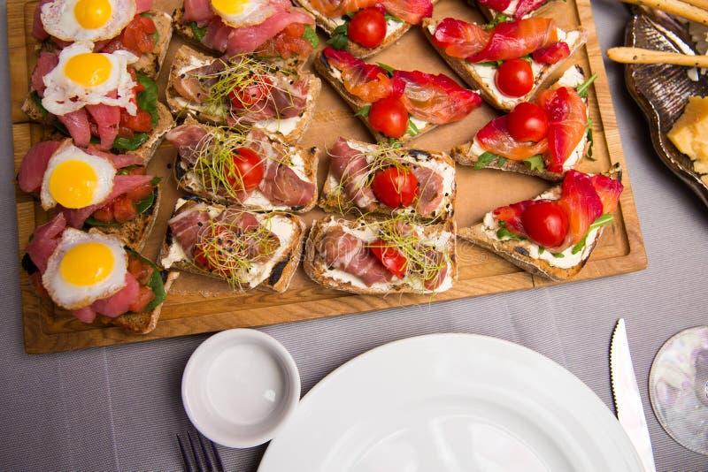 La selección de bruschetta o de canapes sabrosos en el baguette y el queso taosted del quark remató con el salmón ahumado, las ac fotos de archivo