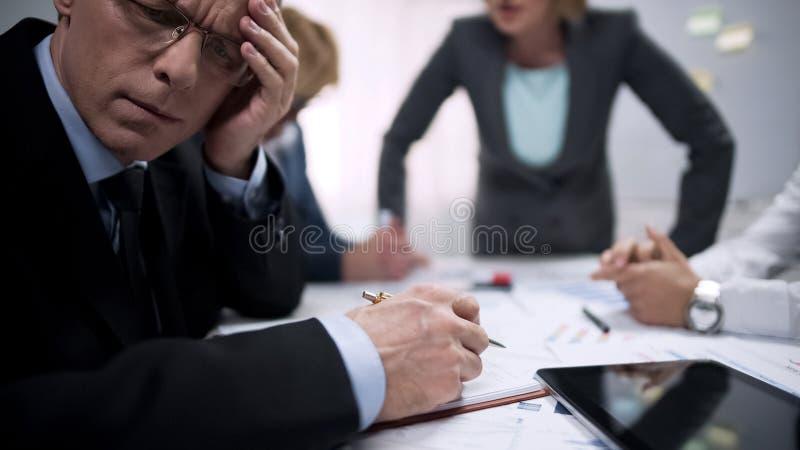 La sensación cansada del oficinista asustó, sufrimiento en la reunión con el jefe de la señora del terror fotos de archivo