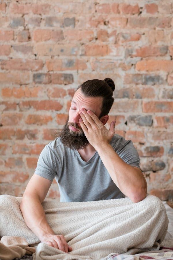 La sensación de la cama del hombre del trastorno del sueño cansó soñoliento foto de archivo libre de regalías