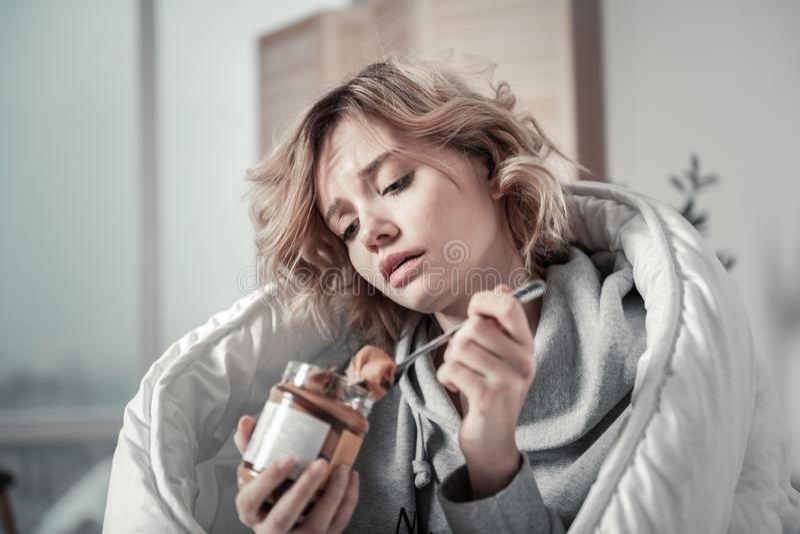 La sensación infeliz joven de la goma del chocolate de la consumición de la mujer subrayó imagen de archivo libre de regalías