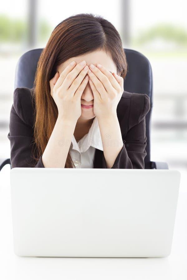 La sensación joven de la mujer de negocios la agotó y cubre los ojos imagenes de archivo