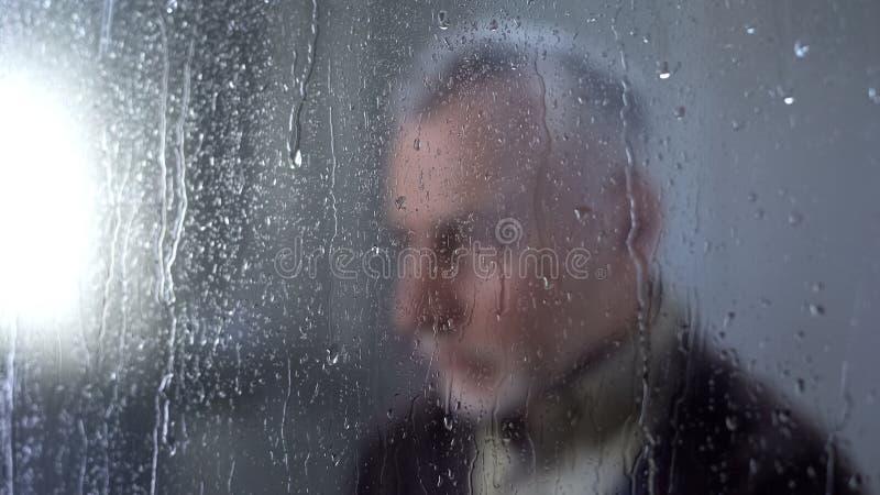 La sensación masculina triste sola, lluvia del pensionista cae el vidrio de la ventana, melancolía, problema fotografía de archivo libre de regalías