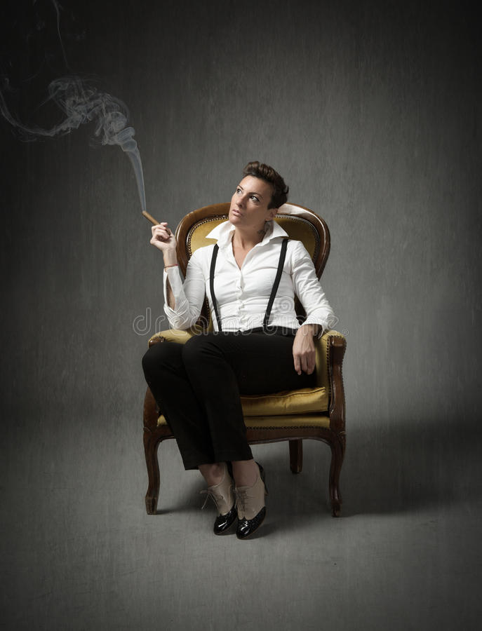 La sentada de la mujer y fuma imagen de archivo libre de regalías